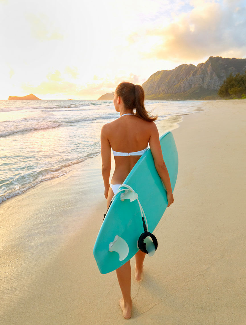 woman with surfboard walking on the beach
