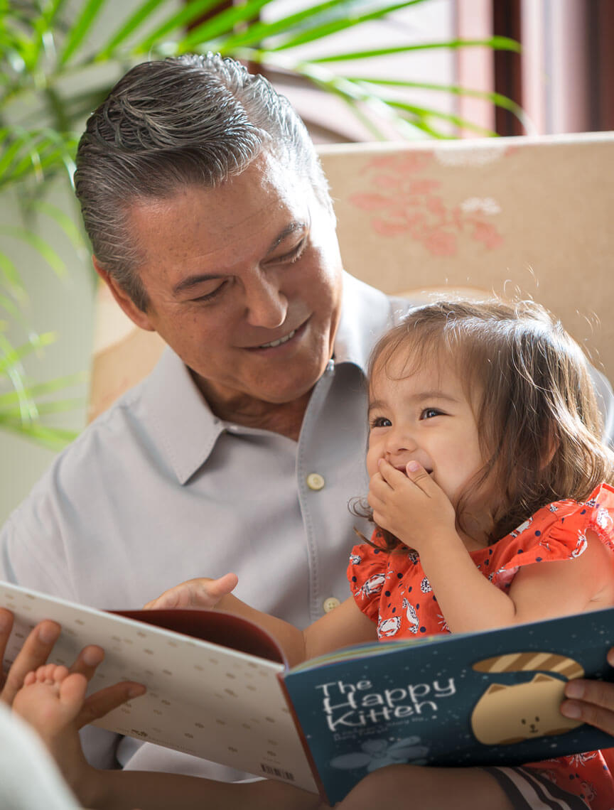 grandfather reading to grand daughter