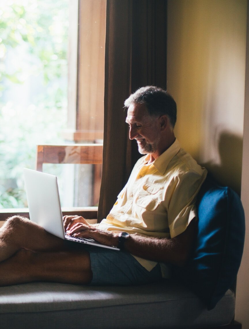 man sitting by window with laptop