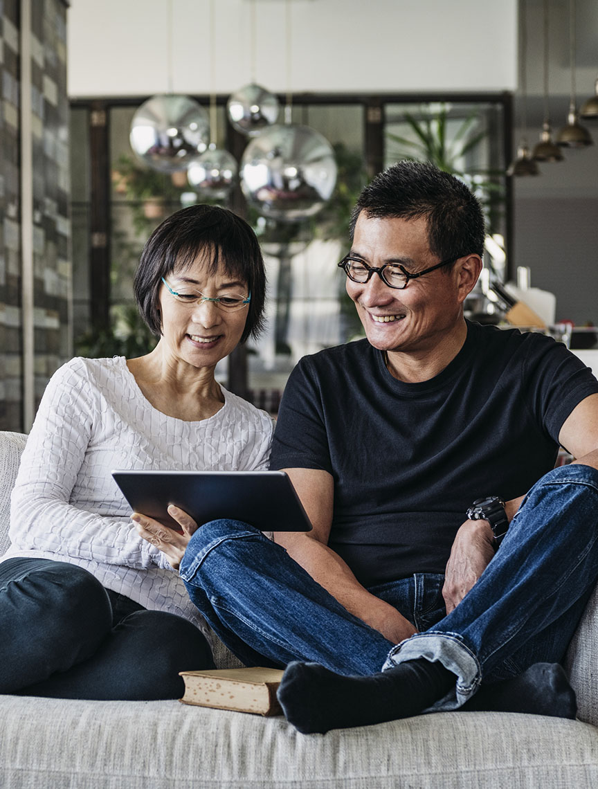couple sitting on couch looking at tablet