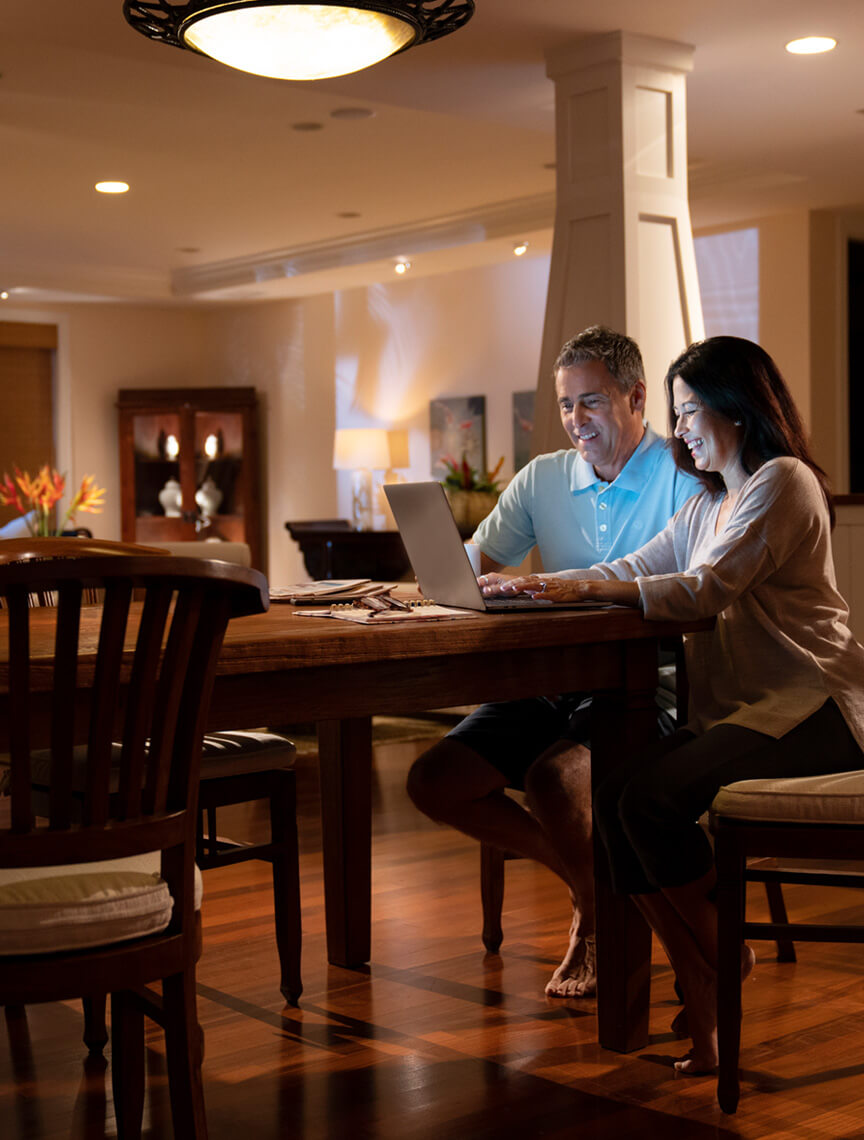couple in dining room using laptop