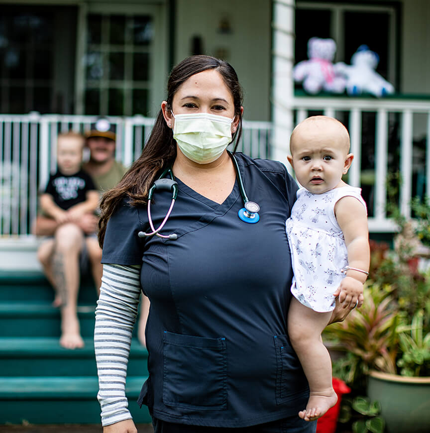 nurse with mask on carrying baby